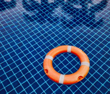 Orange lifebuoy floating on the water surface of the swimming pool against reflection of the palm trees.