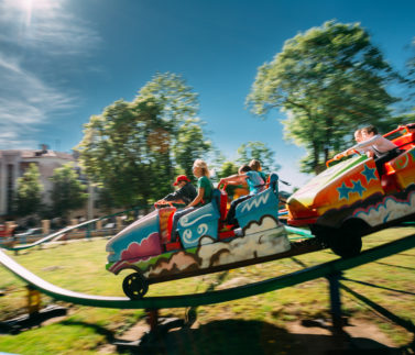 People Having Fun On Rollercoaster In Park. Photo With Zoom Blur For Motion Effect