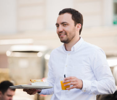 Portrait of happy waiter holding breakfast meal and orange juice at outdoor cafe.