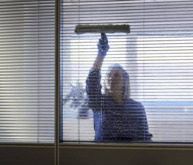 Woman at work, professional female cleaner cleaning and wiping window in office with detergent